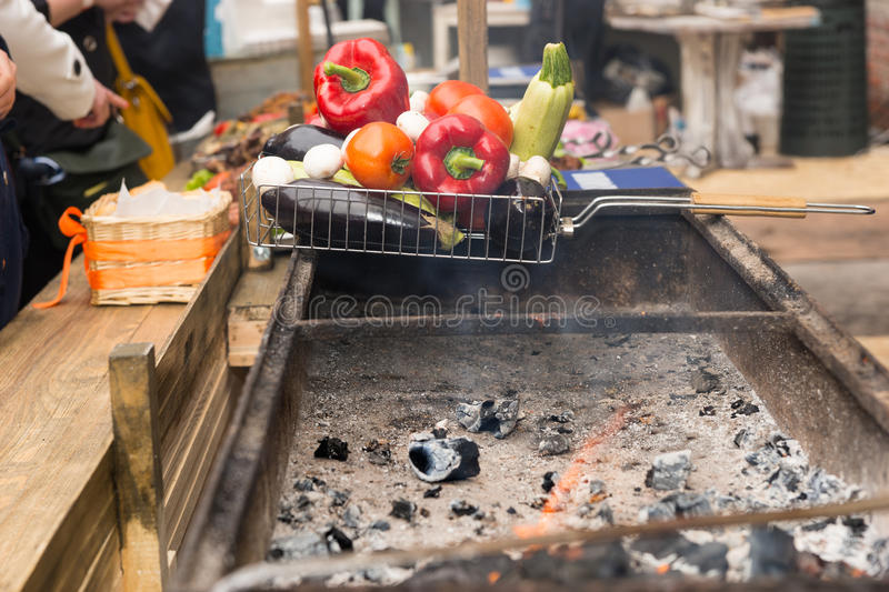Hot coals in a barbecue with fresh vegetables stock images