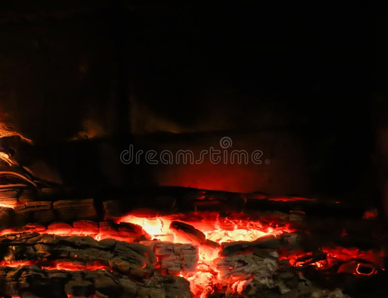 Hot coals of burned wood in the fireplace on a black background. Space for copy, text, your words. Horizontal.  royalty free stock photography
