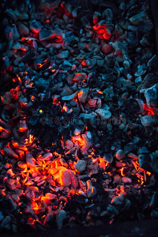 Hot coals and burning woods in bbq grill. Glowing and flaming charcoal, barbecue pit, bright red fire and ash. Weekend recreation background. Close-up, top royalty free stock images