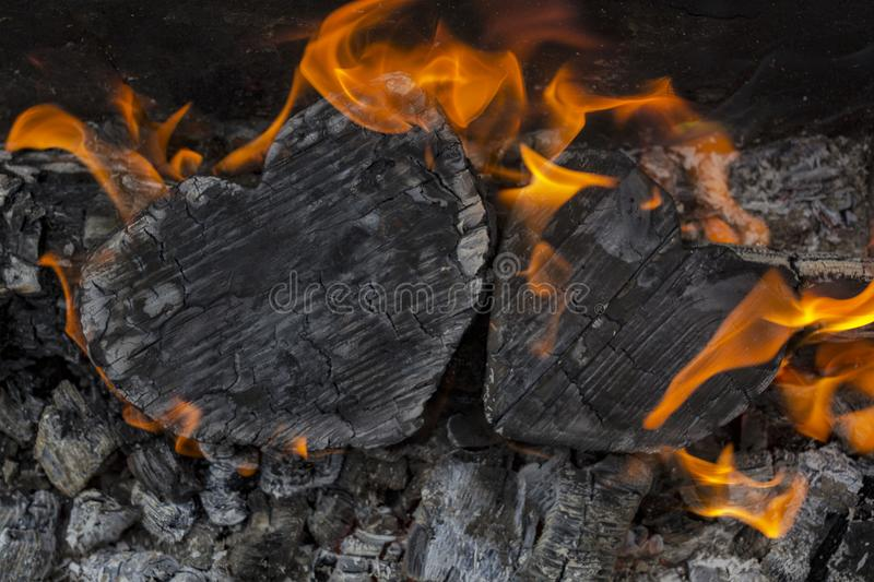 Hot coals and burning woods in the form of human heart. Glowing and flaming charcoal, bright red fire and ash. .Close-up.  royalty free stock images