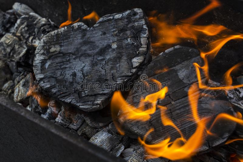 Hot coals and burning woods in the form of human heart. Glowing and flaming charcoal, bright red fire and ash. .Close-up.  royalty free stock photography