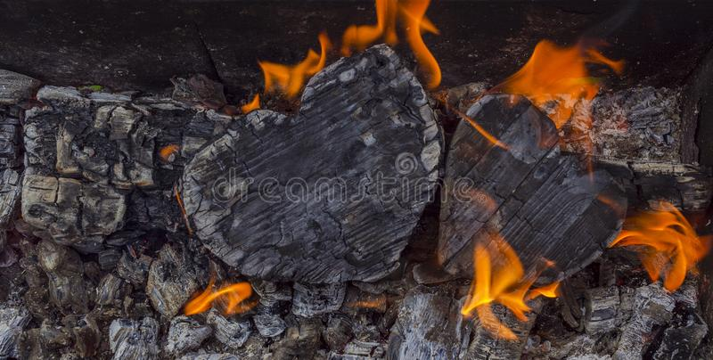 Hot coals and burning woods in the form of human heart. Glowing and flaming charcoal, bright red fire and ash. .Close-up.  stock photography
