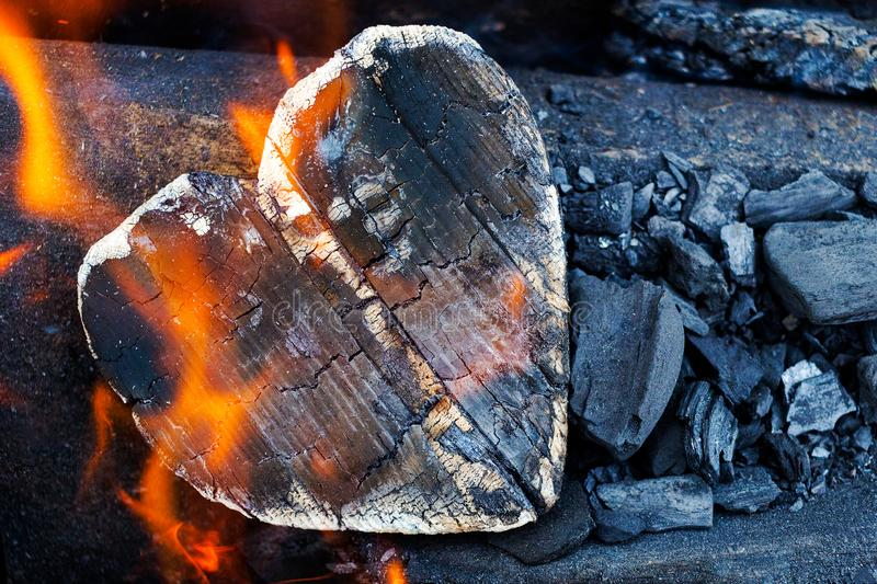 Hot coals and burning woods in the form of human heart. Glowing and flaming charcoal, bright red fire and ash. .Close-up, top view. Hot coals and burning woods stock photography