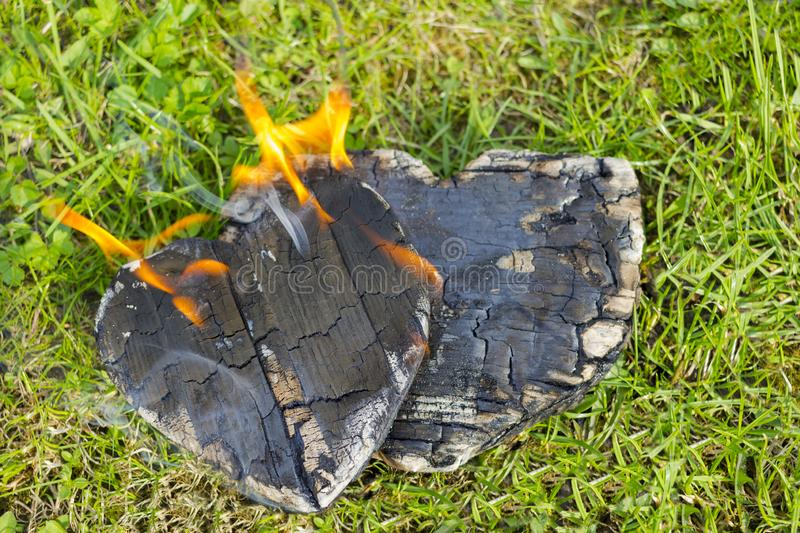 Hot coals and burning woods in the form of human heart. Glowing and flaming charcoal, bright red fire and ash. .Close-up, top view. Hot coals and burning woods stock image