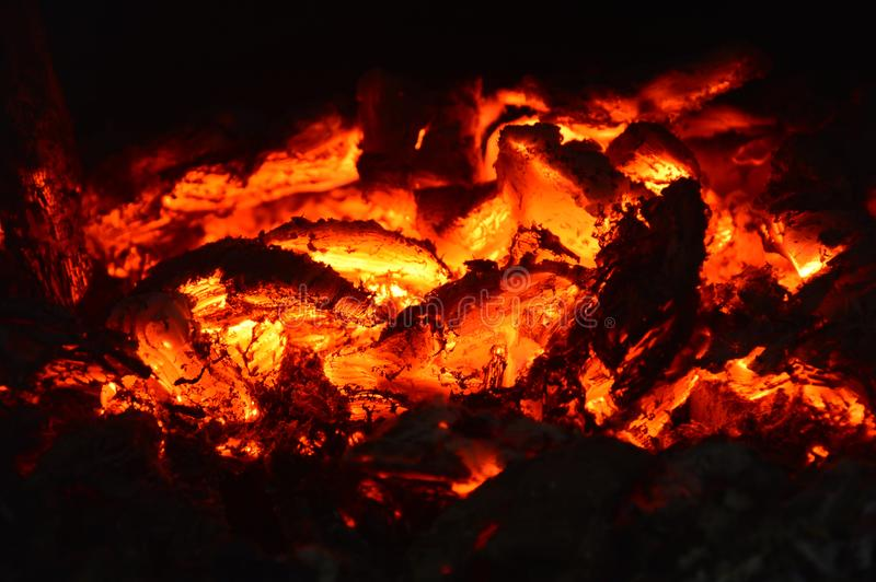 The hot coals of a fire. Burning coals in the oven. Orange Heat. From the fire comes a very strong heat. Horizontal photography royalty free stock image