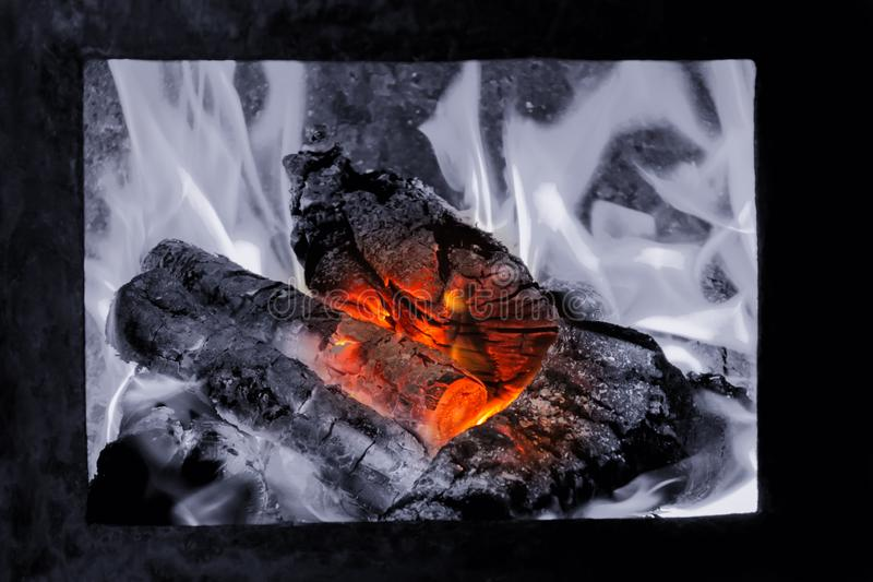 Hot coals in the fire, tongues of flame rise over firewood. Hot coals in the fire, tongues of flame rise over firewood stock image