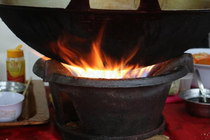 Hot coals that heat up the pan to cook well. Need good skill too stock images