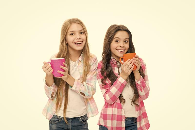 Hot cocoa recipe. Children drink enough during school day. Make sure kids drink enough water. Girls kids hold cups white. Background. Sisters hold mugs stock photography