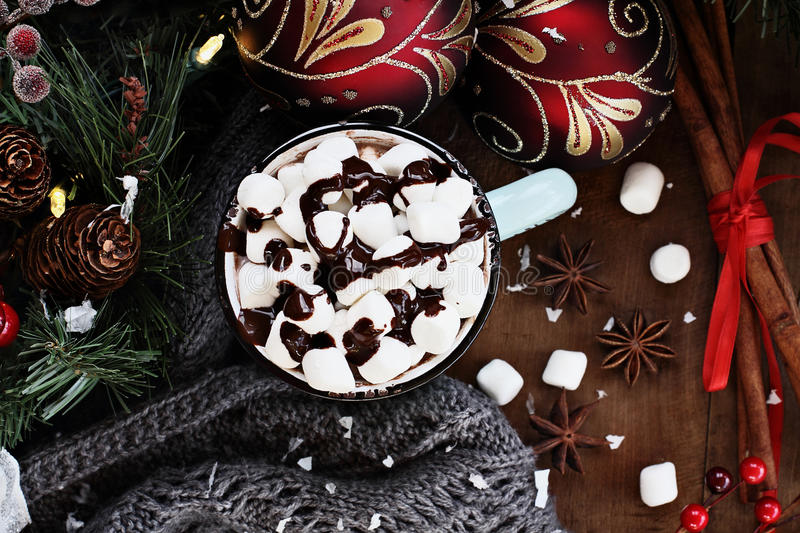 Hot Cocoa with Tiny Marshmellows and Chocolate Sauce. Enamel cup of hot cocoa for Christmas with mini marshmallows and garnished with chocolate sauce. Surrounded stock photography