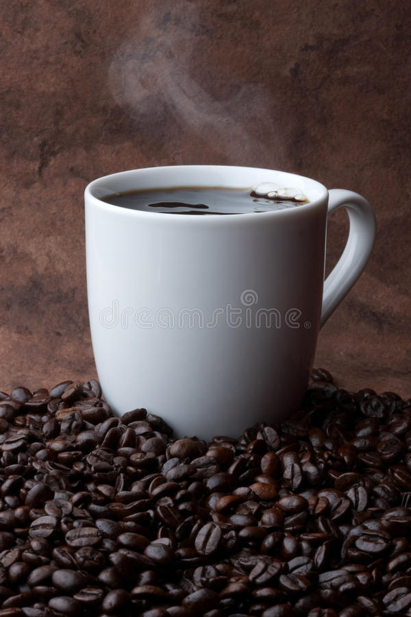 Hot Coffee. Steaming hot cup of coffee sitting in a pile of coffee beans with space for copy royalty free stock photo