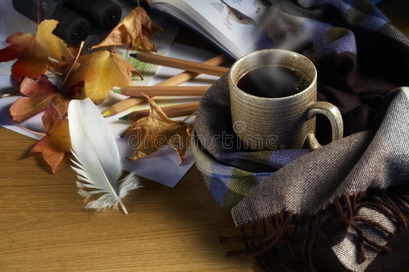 Hot coffee, Autumn leaves, crayons, feather, and a drawing on wood background royalty free stock photo