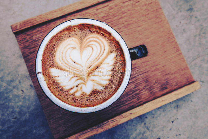 Hot coffee with beautiful coffee art, vintage tone royalty free stock image