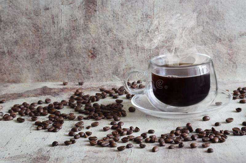 Hot coffee in a beautiful transparent Cup, coffee beans scattered chaotically on a vintage gray background stock photography