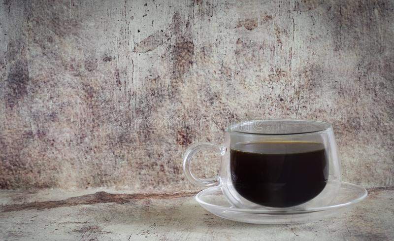 Hot coffee in a beautiful transparent Cup with a glass saucer photographed close-up on a vintage gray background stock photography