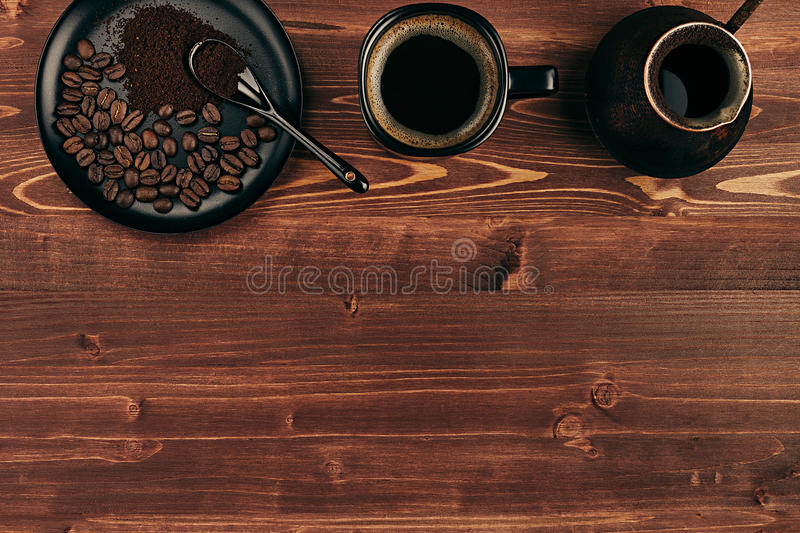 Hot coffee in black cup with beans, spoon and turkish pot cezve with copy space on brown old wooden board background, top view. royalty free stock image