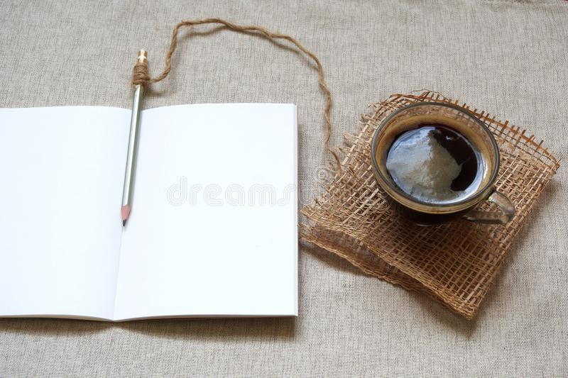Hot coffee and blank notebook for a morning journaling routine. Hot black coffee sitting next to a blank notebook and pencil for a morning journaling routine royalty free stock images