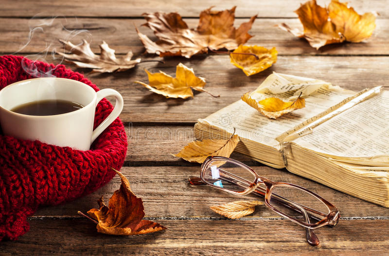 Hot coffee, book, glasses and autumn leaves on wood background royalty free stock photography