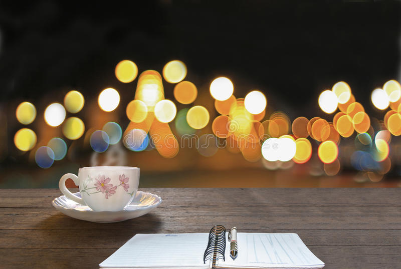 Hot coffee and book on wooden table with colorful bokeh background,concept. royalty free stock images