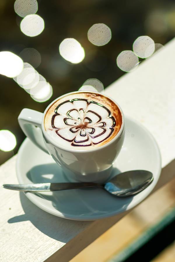 Hot coffee cappuccino in white cup.Morning coffee. white cup of latte hot coffee with leaf, flower pattern, latte art royalty free stock images