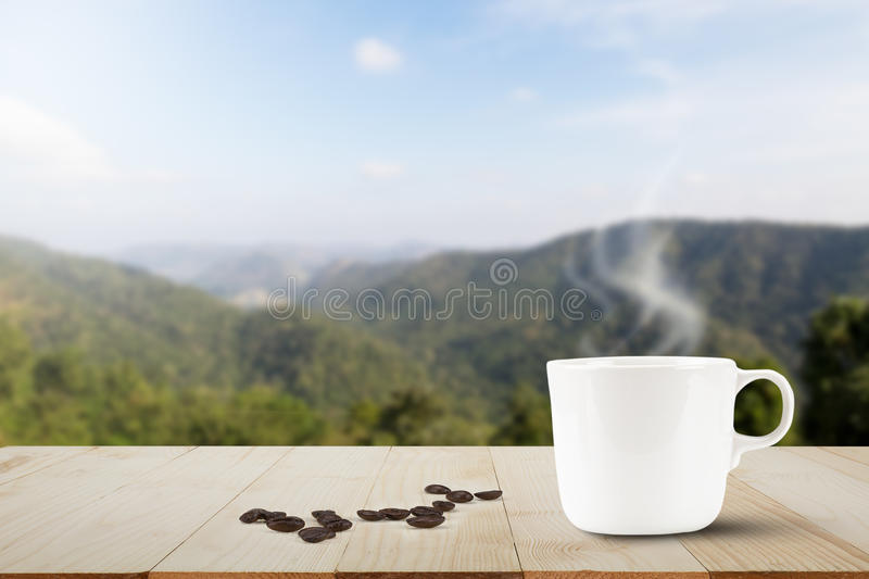 Hot coffee and coffee bean on wooden table top on blu. Hot coffee with steam and coffee bean on wooden table top on blurred mountain background royalty free stock photo
