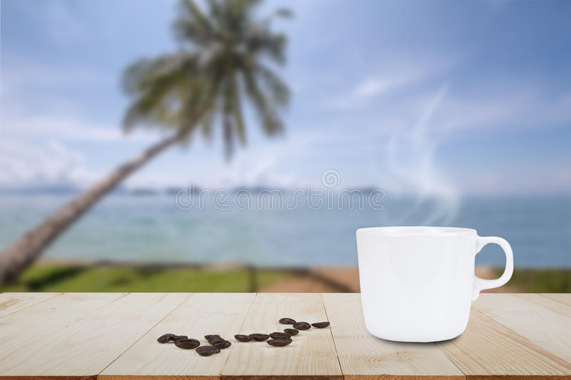 Hot coffee and coffee bean on wooden table top on blurred coconut tree and beach background. Hot coffee with steam and coffee bean on wooden table top on blurred stock photos