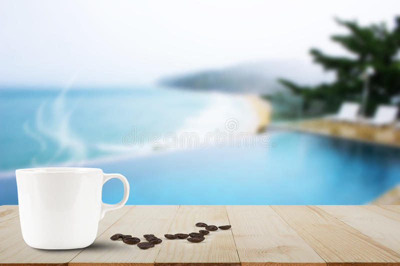 Hot coffee and coffee bean on wooden table top on blurred pool and beach background. Hot coffee with steam and coffee bean on wooden table top on blurred pool royalty free stock images