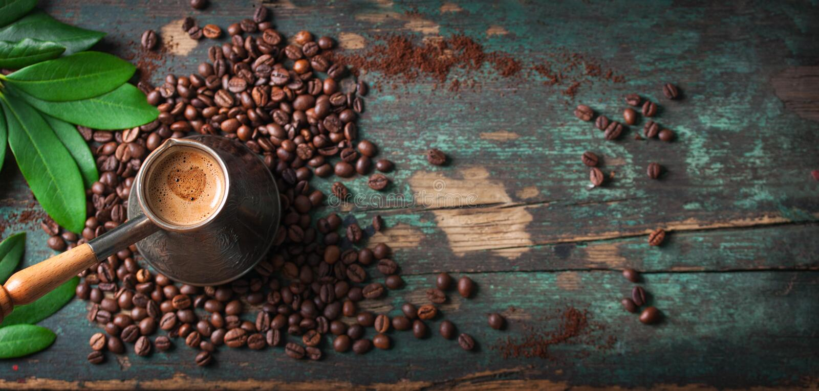 Hot coffee in a coffeepot or turk on a wooden background with coffee leaves and beans, horizontal with copy space stock image
