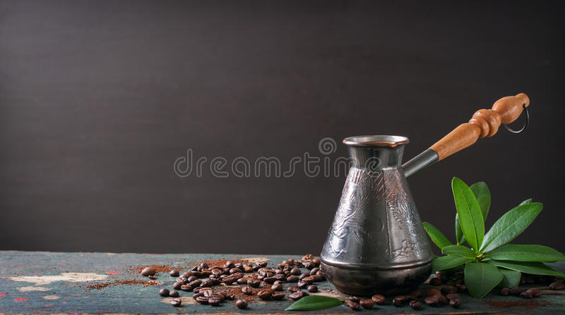 Hot coffee in a coffeepot or turk on a wooden background. With coffee leaves and beans, horizontal with copy space stock image