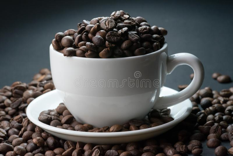 Coffee incup and coffee beans are the background. royalty free stock photos