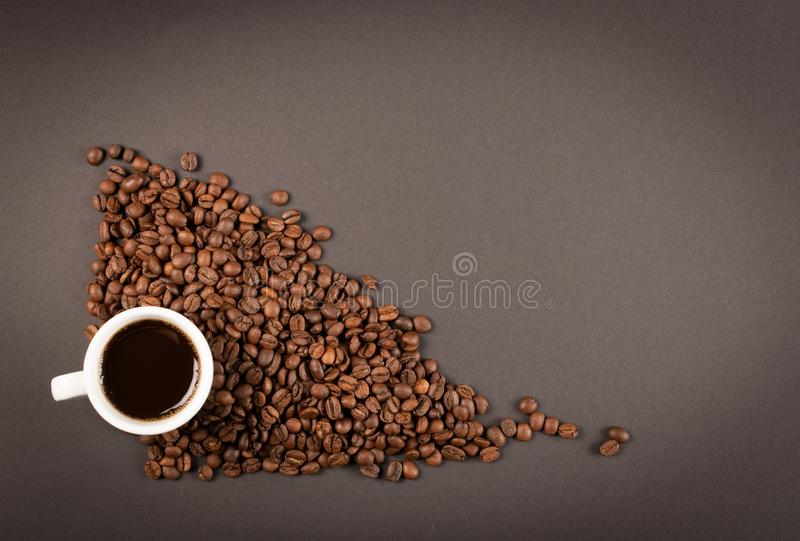 Hot coffee cup and coffee beans on black background top view royalty free stock images
