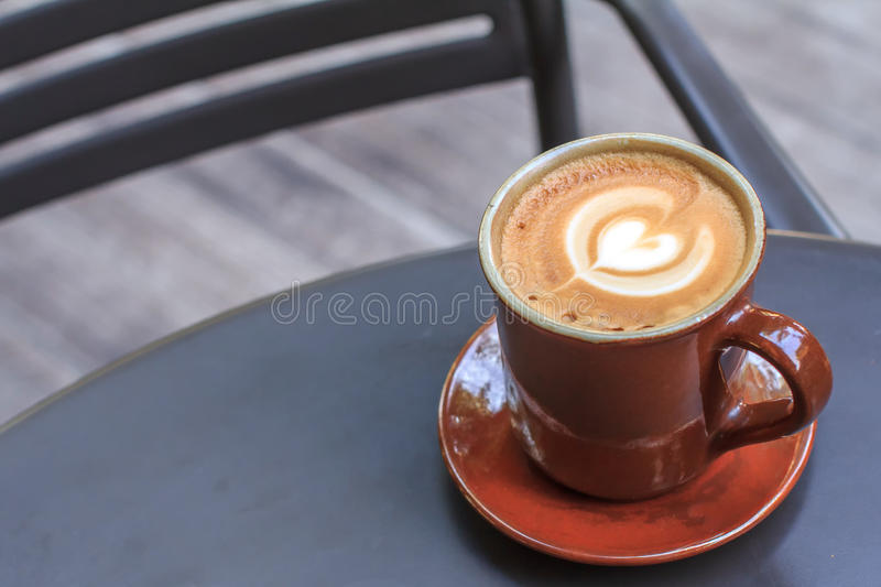 Hot coffee cup on black metal table in coffee shop. stock images