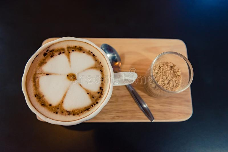 Hot Coffee cup and brown sugar on the wooden tray in coffee shop background with copy space. Hot Coffee cup and brown sugar on the wooden tray in coffee shop stock images