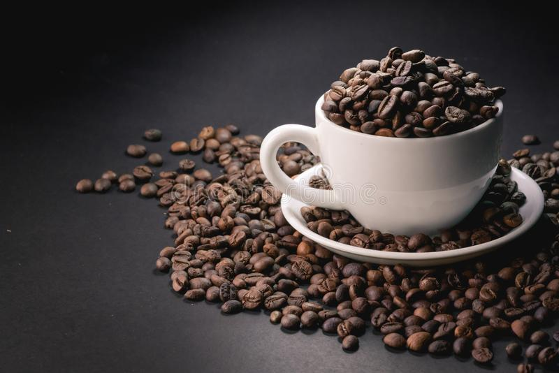 Coffee incup and coffee beans are the background. stock photography