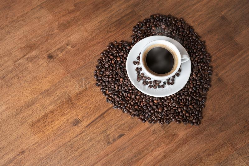 Hot coffee cup with heart pattern of roasted coffee beans stock image