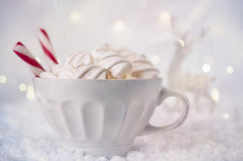 Hot Coffee cup with marshmallows and red candy cane on a frosty winter background. Christmas holidays background. stock photography