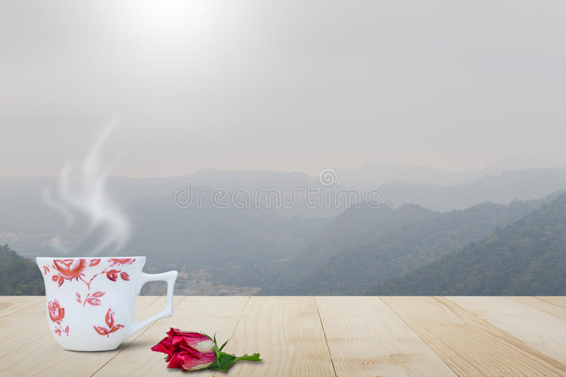 Hot coffee cup with steam and red flower on vintage wooden table top on blurred foggy mountain background stock photography