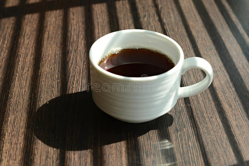Hot Coffee cup on table near windows royalty free stock photography
