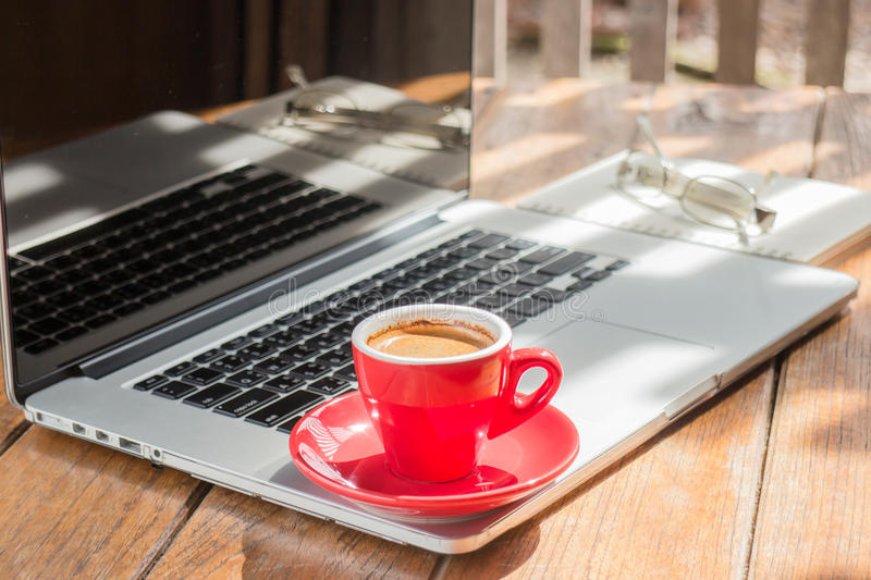 Hot coffee cup on wooden work station. Stock photo royalty free stock photo