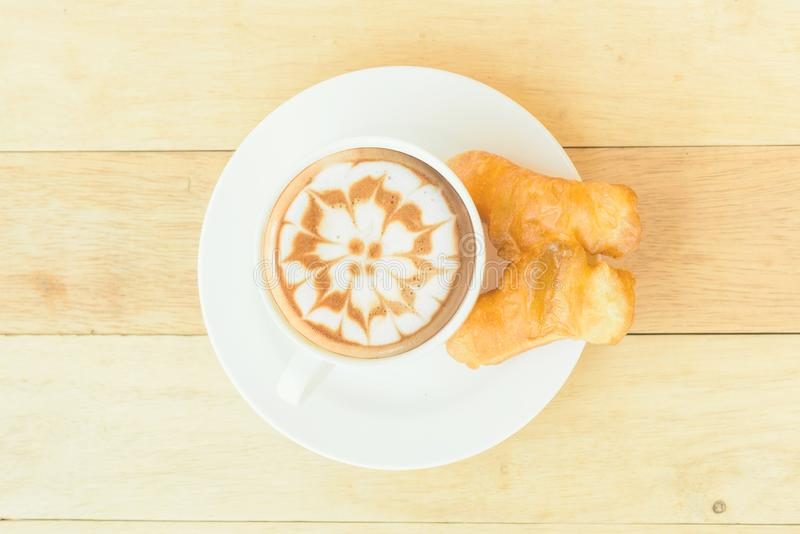 Coffee with deep-fried dough stick on wood table. Hot coffee with deep-fried dough stick / coffee with deep-fried dough stick on wood table royalty free stock photography