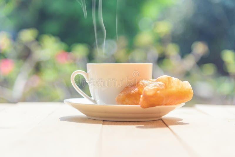 Hot coffee with deep-fried dough stick. / coffee with deep-fried dough stick on wood table stock photography