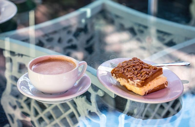 A hot coffee delicious dessert: almond tart with cream, and a cu. P of a hot drink on a beautiful glass table stock photo