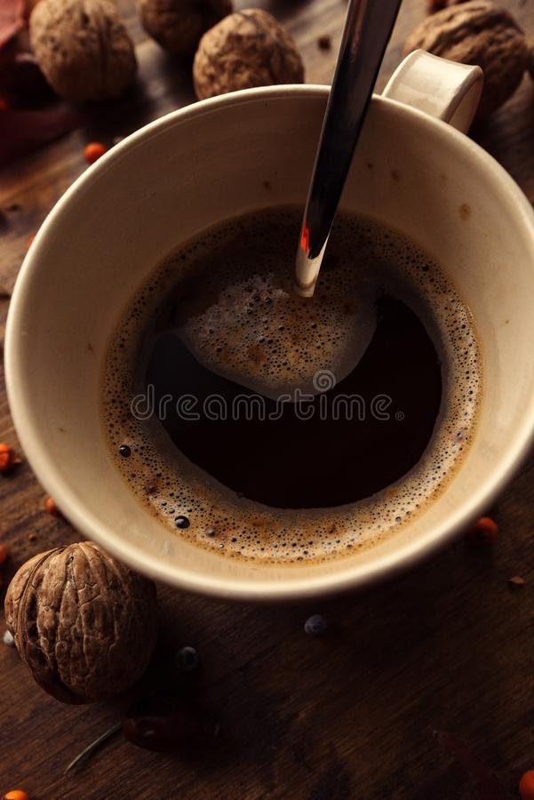 Hot coffee drink for cold autumn days. Top view flat lay of coffee cup on the table decorated with autumnal fruit and dry leaves royalty free stock photos
