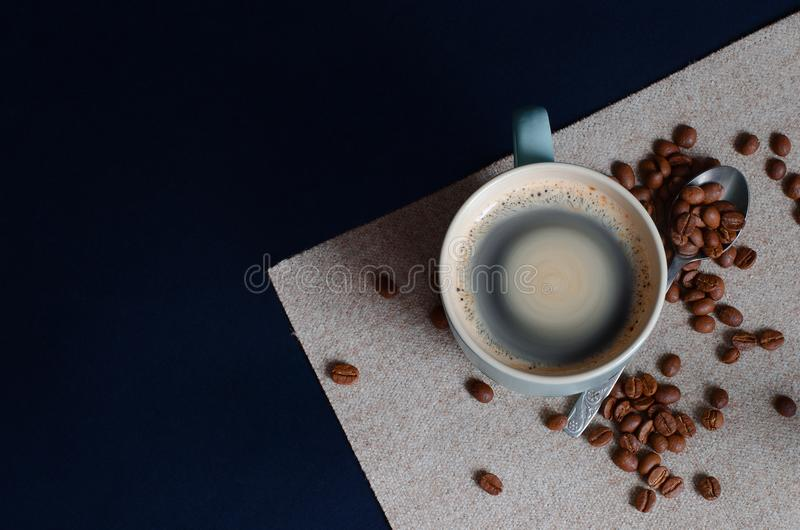 Strong Colombian coffee in a light green cup and whole coffee beans arabica. Top view. royalty free stock photos