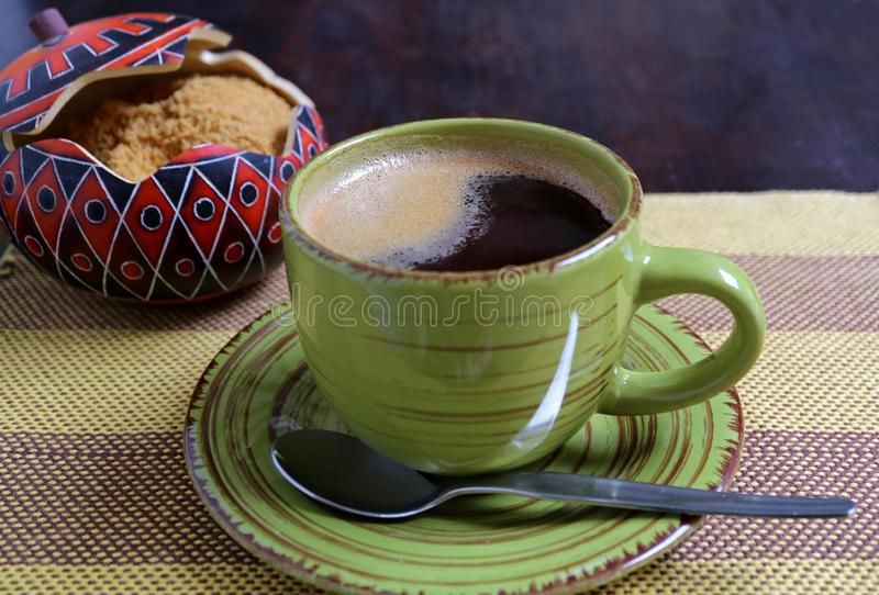 Hot coffee in a green cup with blurred sugar pot of brown sugar in backdrop served on stripe tablecloth. Texture Background royalty free stock image