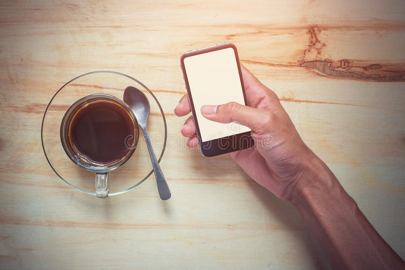 Hot coffee and hand holding mobile phone royalty free stock photography