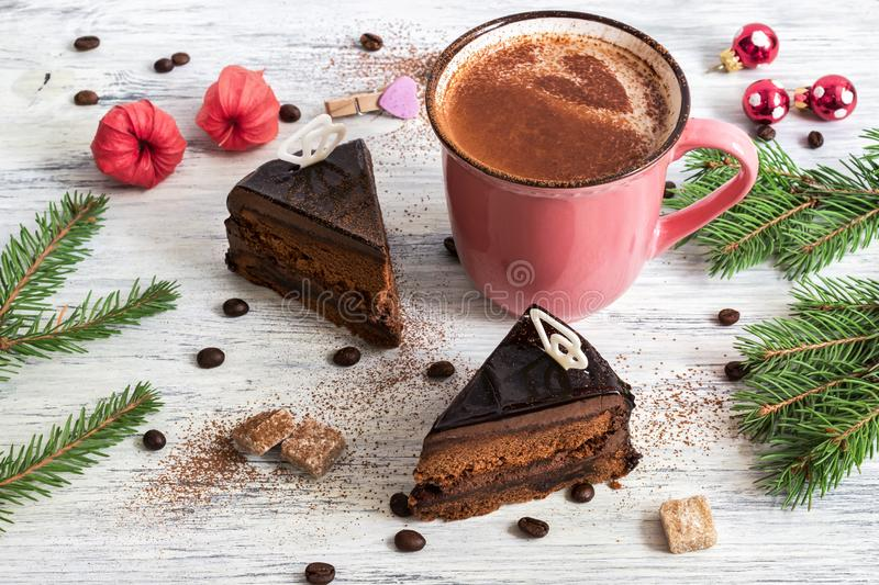 Hot coffee with a heart in a cup of vintage pink color. Two pieces of chocolate cake. Christmas coffee with a cake. stock images