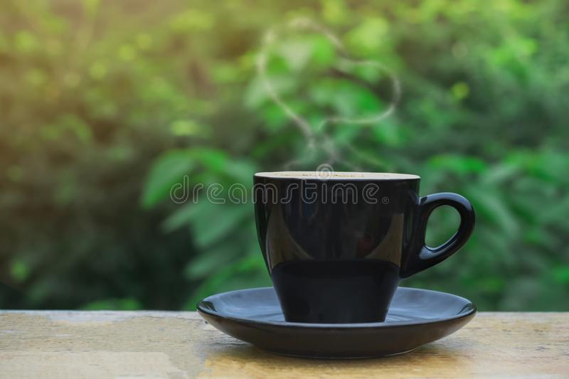 Hot coffee, heart shape smoke in black ceramic cup on wooden table in coffee shop and cafe with green background and flare light, stock photos