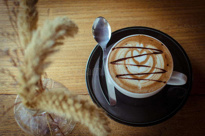Hot coffee with latte art is on the wood table. stock photos