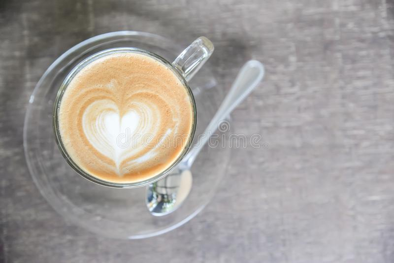 Hot coffee latte with beautiful foam art heart shape on wooden table at coffee shop stock image