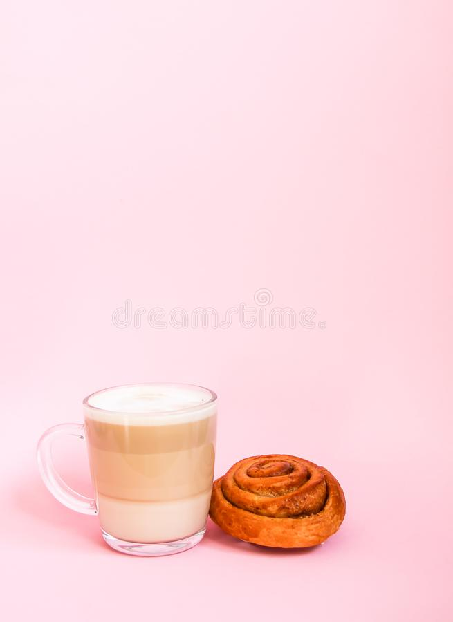 Hot coffee latte transparent glass cup on and sweet cinnamon roll on pink background royalty free stock image